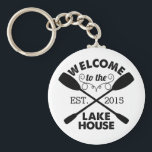 """Welcome to the Lake House Keychain<br><div class=""""desc"""">Start your lake vacation off right with this rustic-chic keychain. Design features &quot;Welcome to the Lake House&quot; in sandblasted black text with a rope illustration and two crossed canoe paddles. Customize with the year you started living life on the lake. Great hostess gift or housewarming present!</div>"""