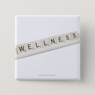 Wellness Spelled On A Word Board Game. Button