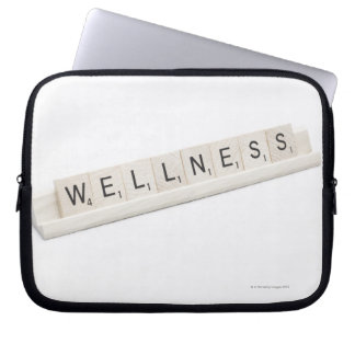 Wellness Spelled On A Word Board Game. Laptop Computer Sleeves