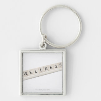 Wellness Spelled On A Word Board Game. Silver-Colored Square Keychain