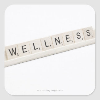 Wellness Spelled On A Word Board Game. Square Sticker