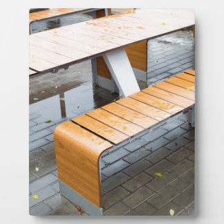 Wet outdoor cafe tables on the street after a rain plaque