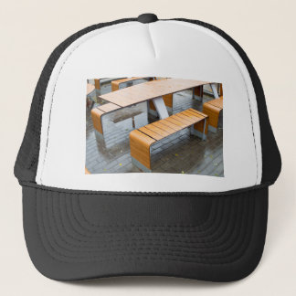 Wet outdoor cafe tables on the street after a rain trucker hat
