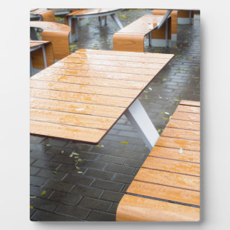 Wet outdoor cafe tables on the street plaque