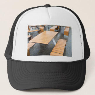 Wet outdoor cafe tables on the street trucker hat