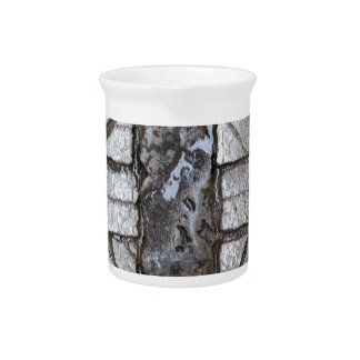 Wet paver blocks of natural stone on a road. drink pitcher