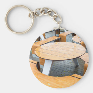 Wet round outdoor cafe tables on the street keychain