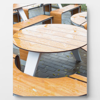 Wet round outdoor cafe tables on the street plaque