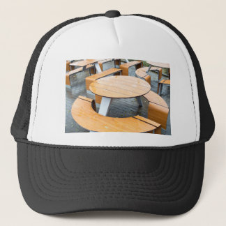 Wet round outdoor cafe tables on the street trucker hat