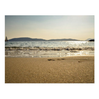 Wet sand and gentle waves with a sailboat in the d postcard