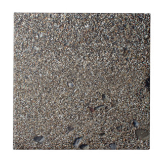 Wet sand and small stones with fragments of shells ceramic tile