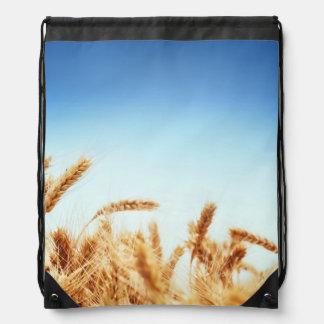Wheat field against blue sky drawstring backpacks