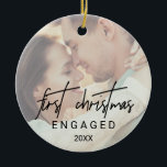 """Whimsical Calligraphy Faded Photo Engaged Ceramic Ornament<br><div class=""""desc"""">This whimsical calligraphy faded photo engaged holiday ornament is the perfect modern Christmas tree decoration. The design features elegant yet rustic typography with two of your photos,  one on the front and one on the back. This keepsake ornament reads """"first Christmas engaged"""". Personalize it with the year.</div>"""