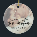 "Whimsical Calligraphy Faded Photo Engaged Ceramic Ornament<br><div class=""desc"">This whimsical calligraphy faded photo engaged holiday ornament is the perfect modern Christmas tree decoration. The design features elegant yet rustic typography with two of your photos,  one on the front and one on the back. This keepsake ornament reads &quot;first Christmas engaged&quot;. Personalize it with the year.</div>"