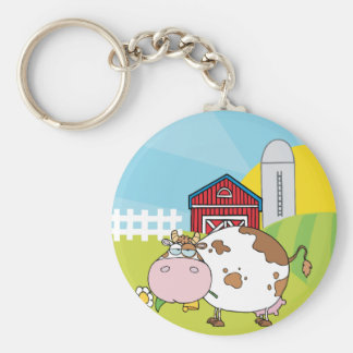 White and brown cow in front of farm scene keychain