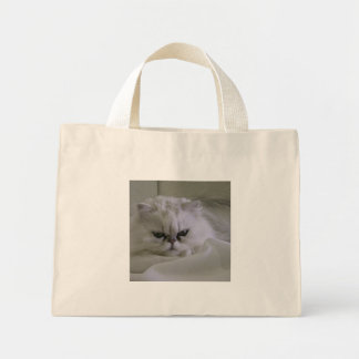 White cat lying on the bed mini tote bag