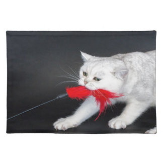 White cat playing pulling red toy cloth placemat
