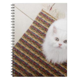 White cat sitting on mat spiral notebook