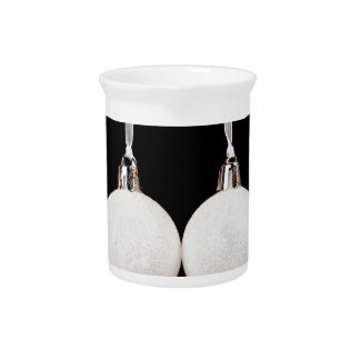 White christmas balls in row on black background beverage pitcher