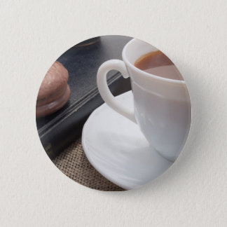 White cup of hot cocoa and a chocolate biscuit button