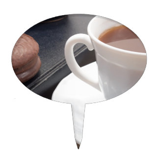 White cup of hot cocoa and a chocolate biscuit cake topper