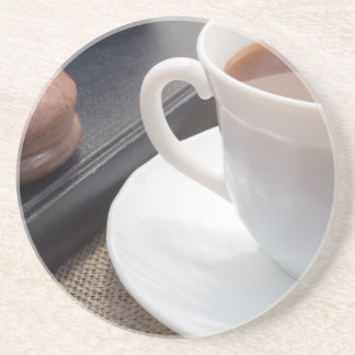 White cup of hot cocoa and a chocolate biscuit drink coaster