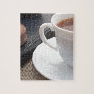 White cup of hot cocoa and a chocolate biscuit jigsaw puzzle