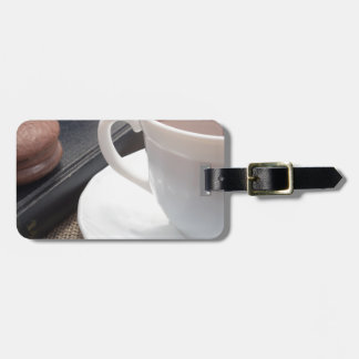 White cup of hot cocoa and a chocolate biscuit luggage tag