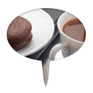 White cup with cocoa and chocolate covered biscuit cake topper