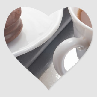 White cup with cocoa and chocolate covered biscuit heart sticker
