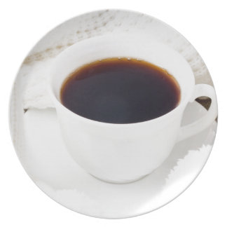 White cup with hot coffee and woolen mittens plate