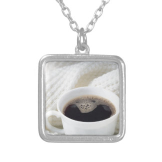 White cup with hot coffee wrapped in a white woole silver plated necklace