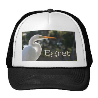 White Egret text backlit looking right against Trucker Hats