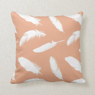 White feather print on soft peach pillow