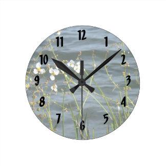 White flowers green stems blue pond back round clock