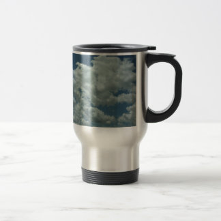 White, fluffy clouds in blue sky travel mug