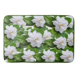 White gardenia flowers and green leaves on green bath mat