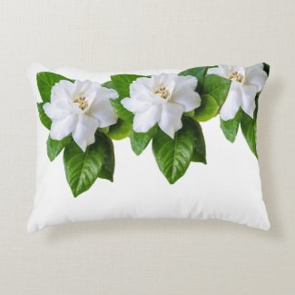 White  gardenia flowers and green leaves on white accent pillow