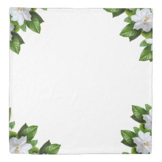 White  gardenia flowers and green leaves on white duvet cover