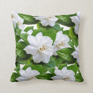White  gardenia flowers and green leaves on white throw pillow