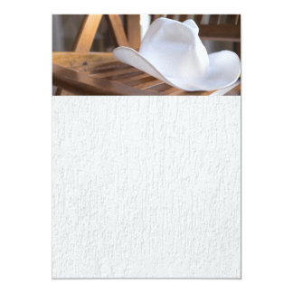 White hat on a wooden chair card