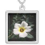 White hibiscus flower red center dark background necklace