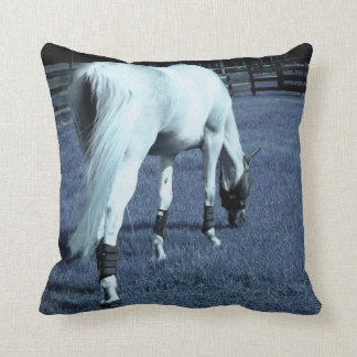 white horse blue grazing head down in grass throw pillow