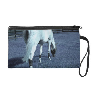 white horse blue grazing head down in grass wristlet purse