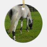 white horse grazing head down in grass ornament