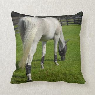 white horse grazing head down in grass throw pillow