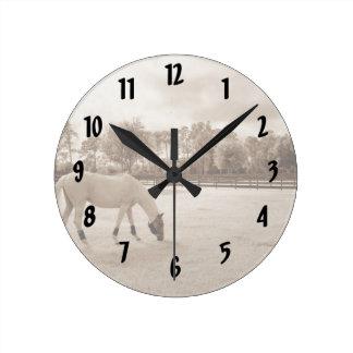 white horse in pasture grazing sepia round clock