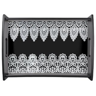 White lace forms a delicate border against black serving platters