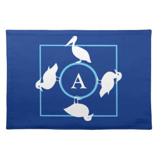 White maritime birds and monogram on dark blue cloth placemat