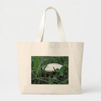 White mushroom on a green meadow jumbo tote bag
